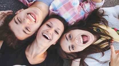 Top view of friends lying down and laughing