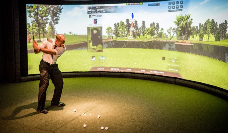 Airline pilot in the middle of golf swing in front of simulated screen in PGA airport lounge, MSP airport.