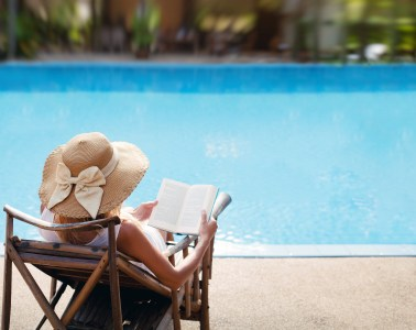 woman reading and relaxing near luxury swimming pool