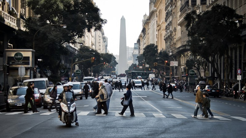 People cross the street in Buenos Aires with the Obelisco de Buenos Aires in the backdrop.