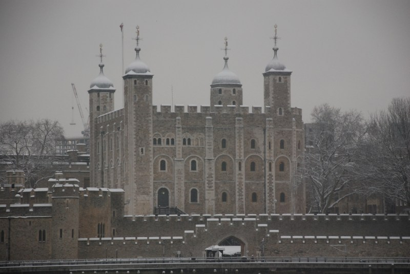 The historic Tower of London in the grey dreary winter covered in snow.