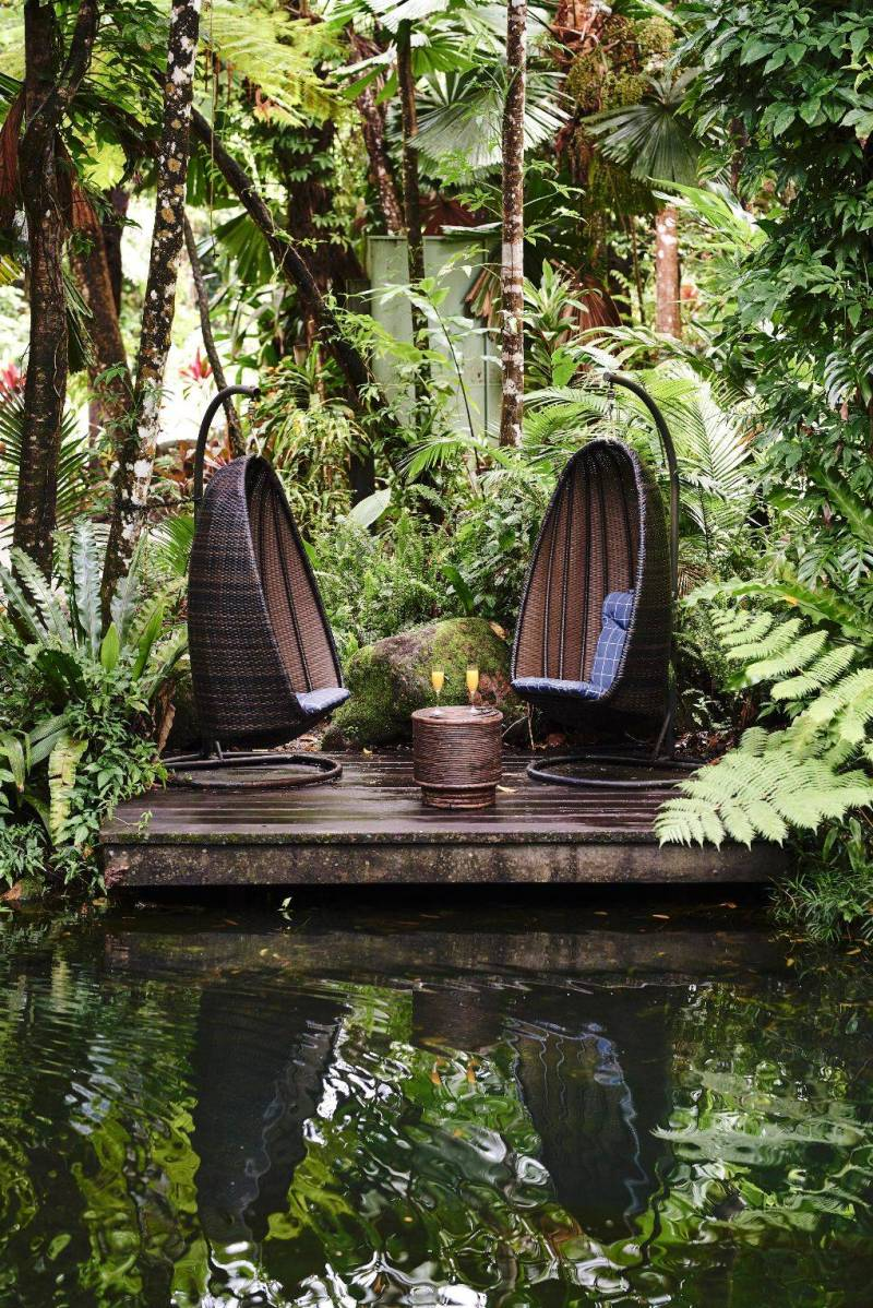 Oval-shaped pod seats with candle on table and foliage and a pond nearby.