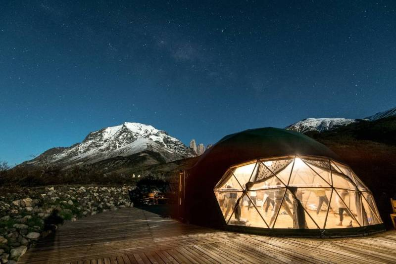 People doing yoga in lit up interior dome at night in mountains.
