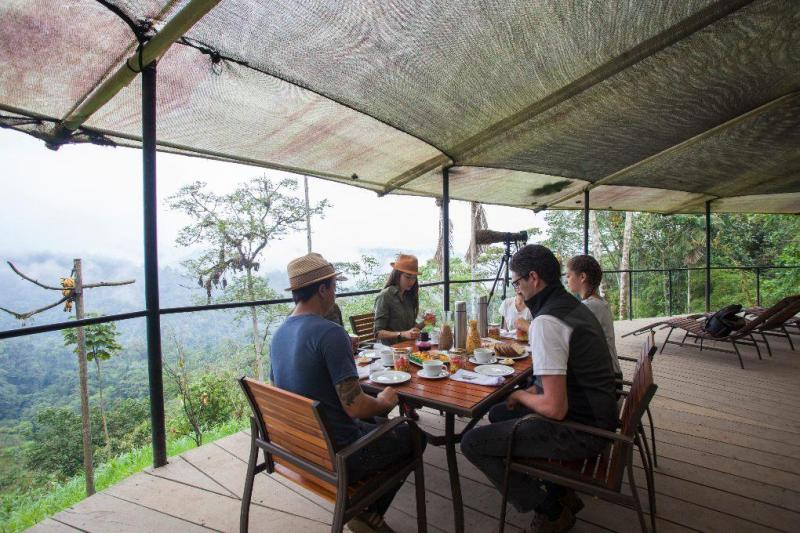 People eating breakfast on deck overlooking the rain forest.