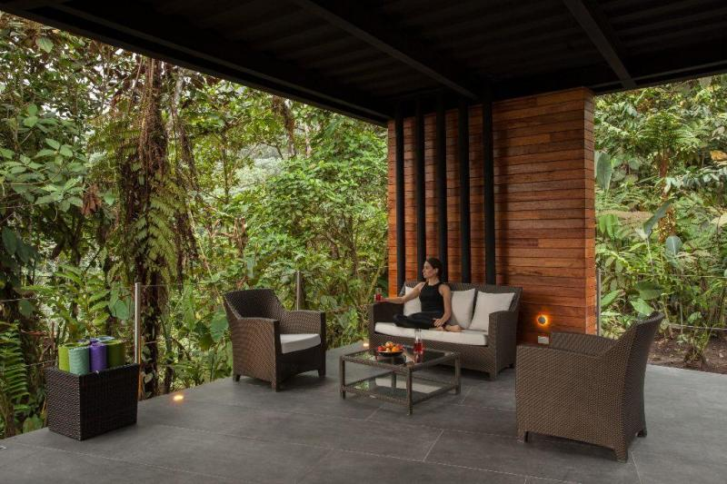 Woman sitting with open-wall view of rainforest.