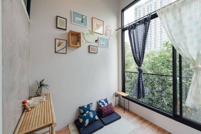 Room with neatly tied curtain and bright light filling in from the window.
