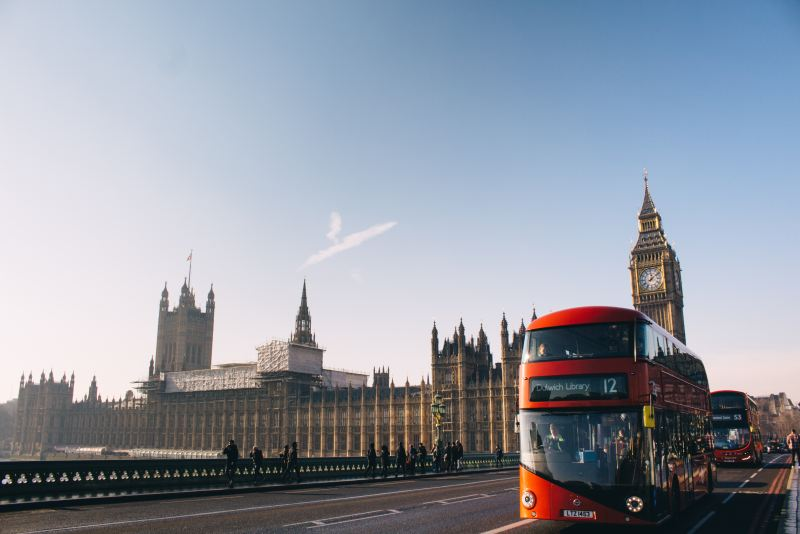 Iconic London double bus on a clear day with Big Ben, aka Elizabeth Tower in the background.