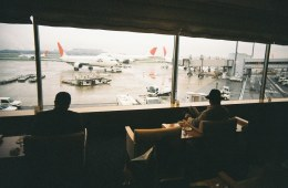 Two men sit in airport lounge looking out at planes on the tarmac.