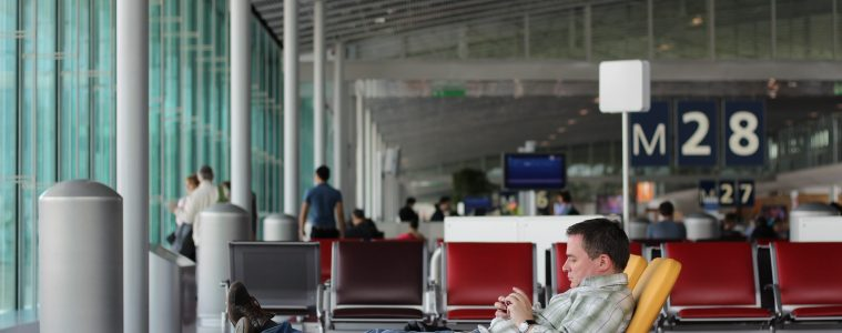 Man lays in lounge chair and looks at phone while waiting in airport.