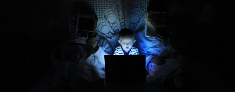 Toddler, or young child, looks at the glow of the blue computer screen at night.