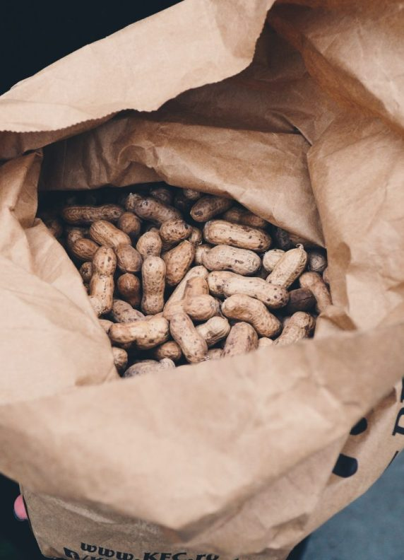 Large amount of peanuts in brown paper bag.
