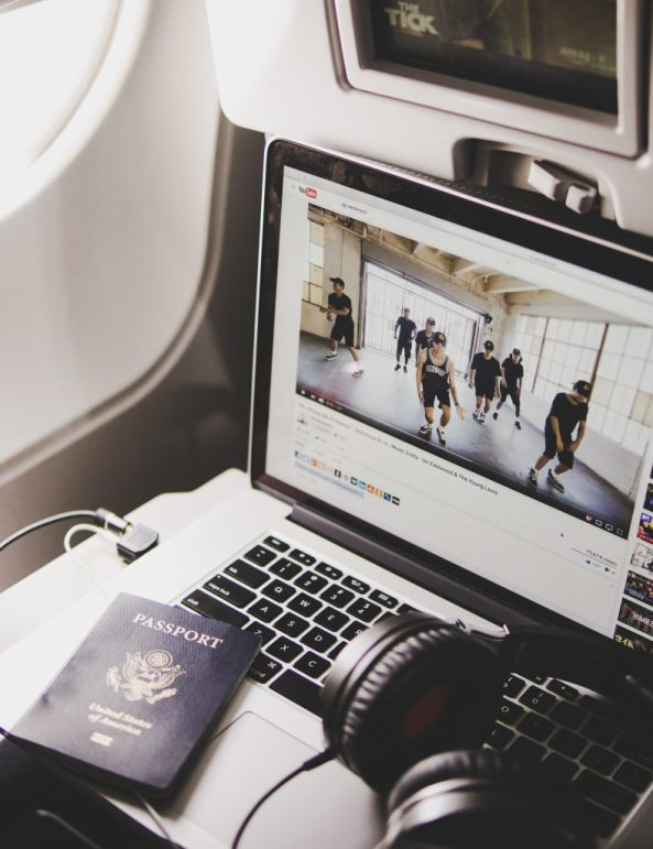 Passenger watches a Youtube video on airplane tray table during a long flight.