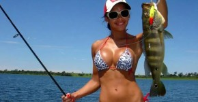 Woman fishing in a bikini top holding a Peacock Bass