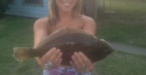 Hot girlfriend holding up a flounder