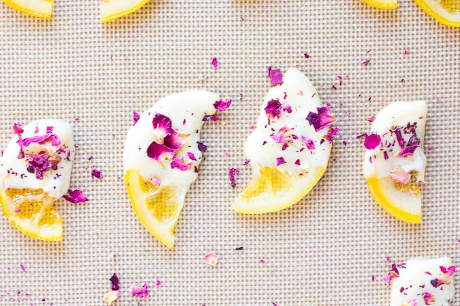 white chocolate candied lemons with edible rose petals on a mat
