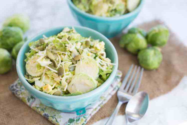blue bowls with silverware and napkins, holding shredded brussels sprouts salad