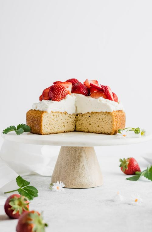head on shot of strawberry almond flour cake on a white cake stand with a large slice cut out.