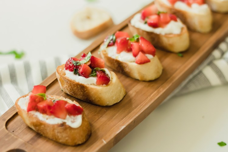 long wooden board covered in strawberry bruschetta sclices