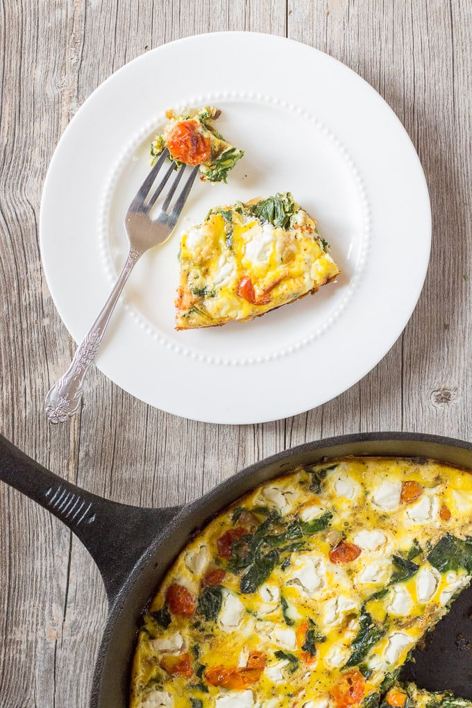 slice of roasted tomato, kale, and goat cheese frittata on a white plate with cast iron skillet toward the bottom