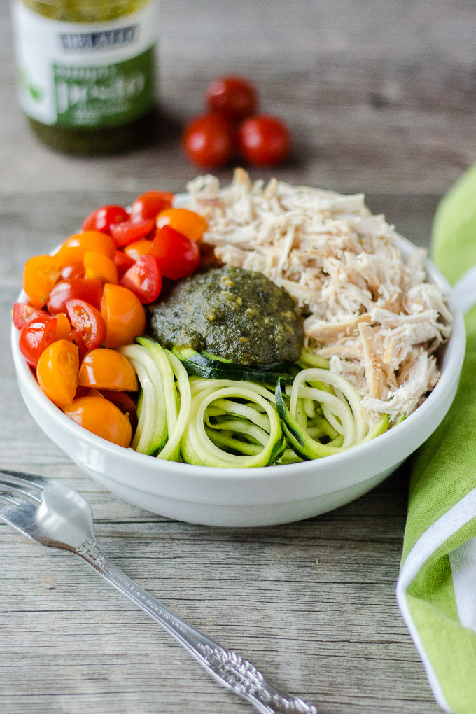 white bowl with pesto, chicken, zoodles, and cut tomatoes on a gray background with a white and green towel on the right, silver fork on the left, and pesto container and 3 cherry tomatoes in the background