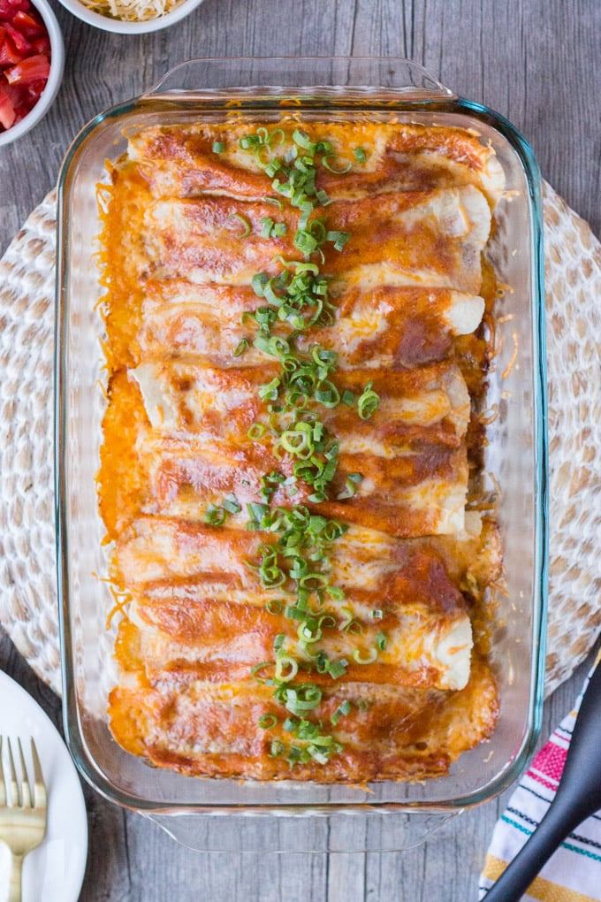 gluten free cheesy chicken enchiladas in a 9x13 baking dish on a round woven placement surrounded by props