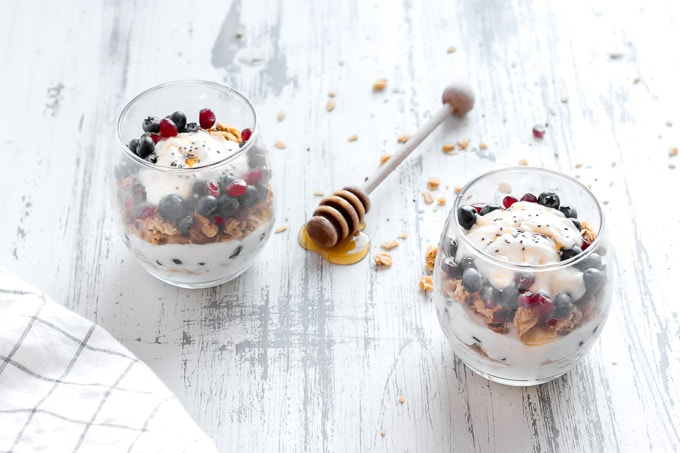 two clear glasses with breakfast yogurt parfait in them,. A white towel with thin black square outlines is in the bottom left corner and a honey dipper with honey drizzling off it is in between the two glasses