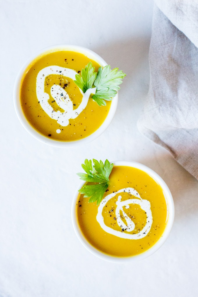 two white bowls with curried butternut squash soup with a swirl of coconut milk and black ground pepper on top. On a slightly gray marble background with a grayish-tan towel to the right.