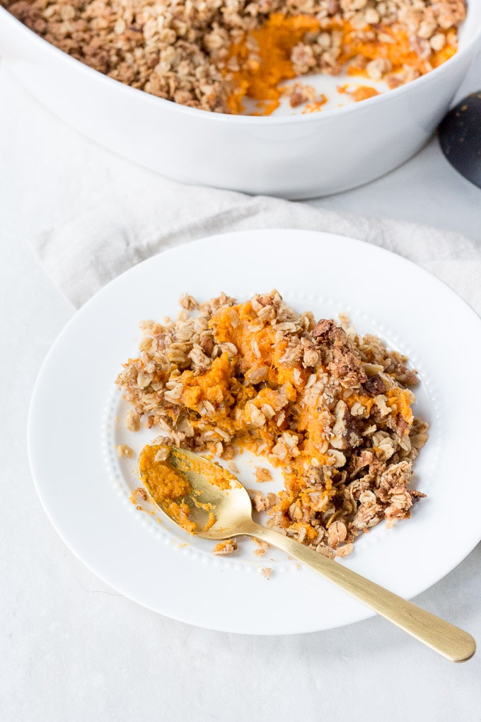 white plate with sweet potato casserole on it and a gold spoon dug into it. A white casserole dish is in the background with a black serving spoon