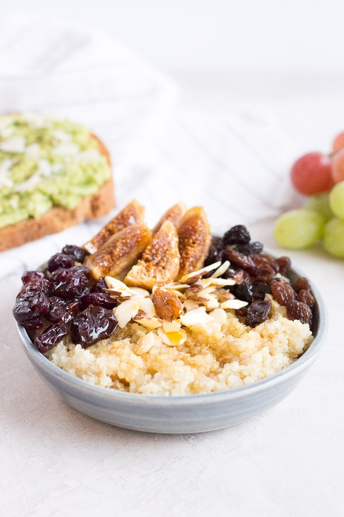 a 45 degree angle shot of quinoa breakfast bowl with avocado toast on a napkin in the upper left, grapes in the upper right, and a napkin and spoon in the bottom right.