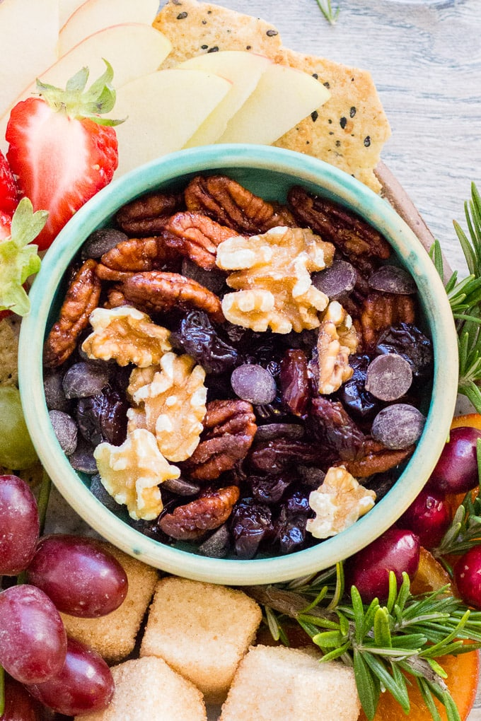 top down shot of gluten free trail mix in a small teal bowl on a snack plate