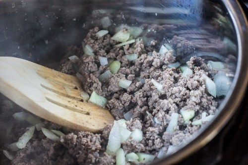side shot of ground beef and chopped white onion being cooked in an instant pot