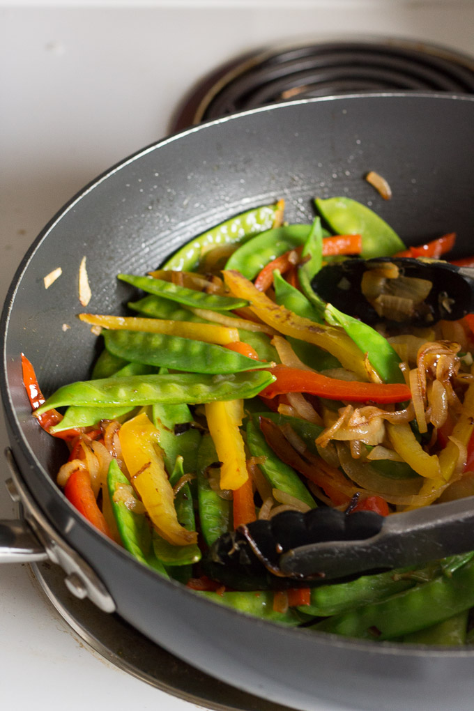 cooked onion and bell pepper slices in a large frying pan with snow peas and a pair of tongs