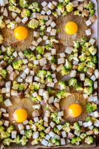 top down view of 4 eggs in wells with cubed pototoes and romanesco on a sheet pan