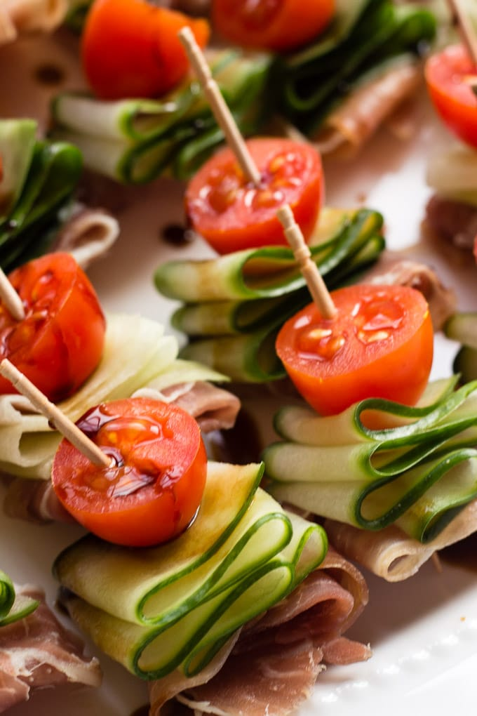 close up shot of cucumber bites with halved tomatoes, cucumber ribbons, and prosciutto on a toothpick