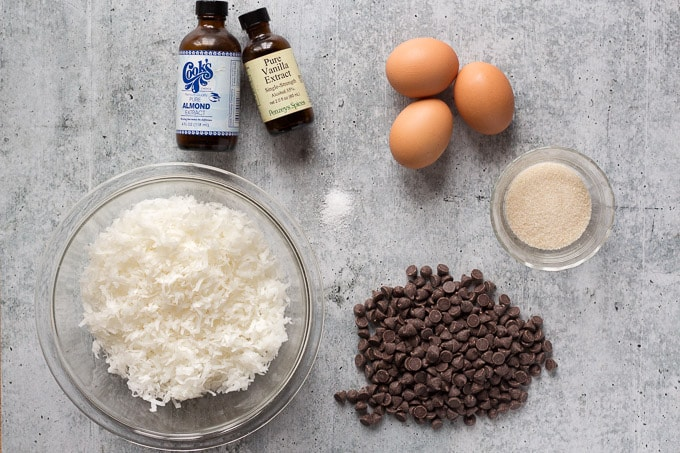 top down shot of ingredients for chewy coconut macaroons - extracts, eggs, sugar, coconut, chocolate chips, and salt