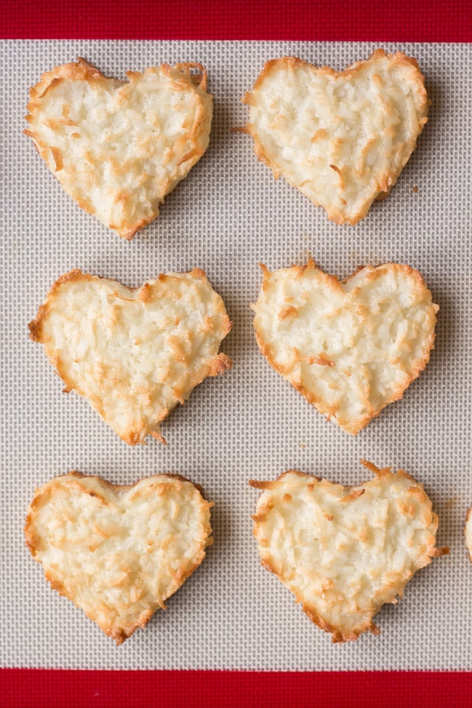 top down view of cooked chewy coconut macaroon hearts on a silicone baking mat