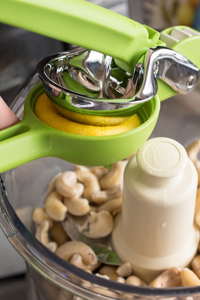 half a lemon being squeezed by a juicer into a food processor with cashews in it