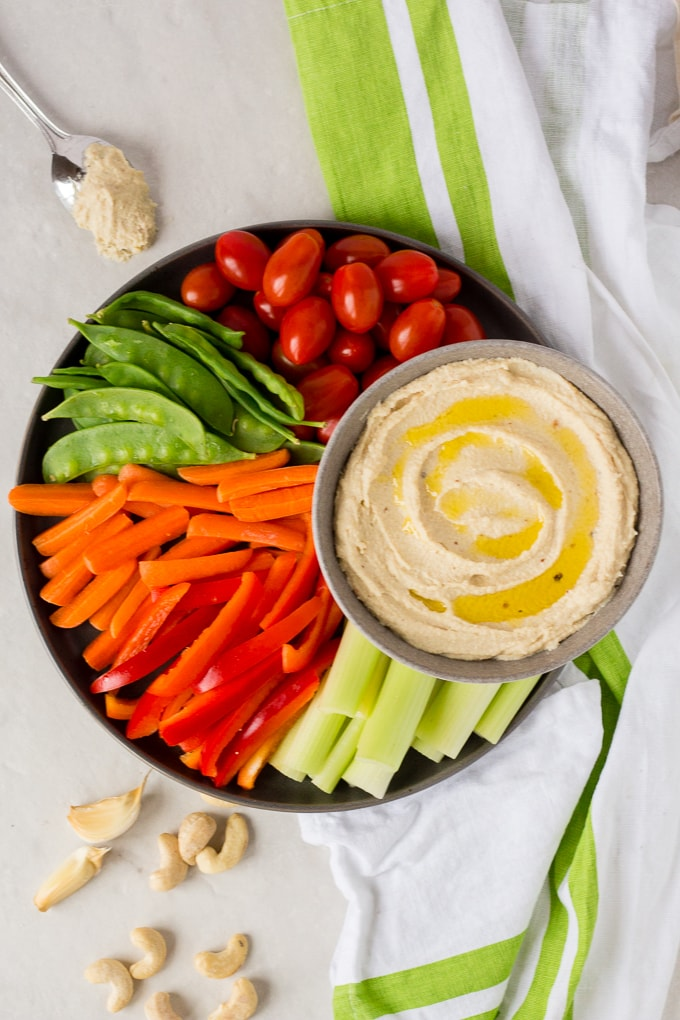 top down view of roasted garlic cashew dip on a plate with veggies
