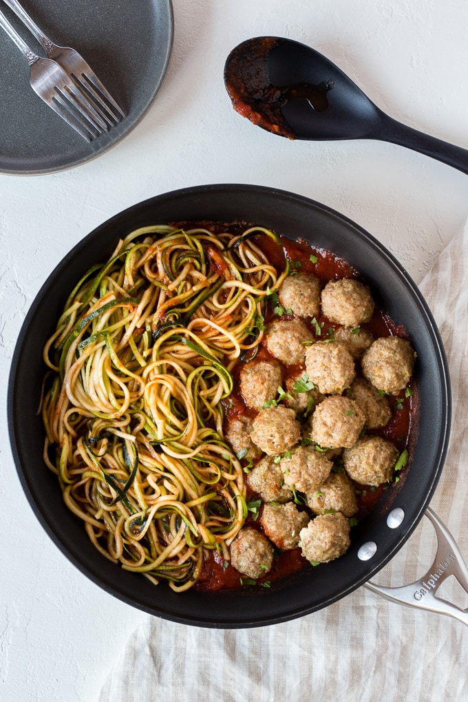 top down view of baked paleo turkey meatballs in a skillet with marina and zucchini noodles with a plate and black large spoon nearby