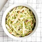 top down view of healthy apple and broccoli slaw in a white dish with a checked towel