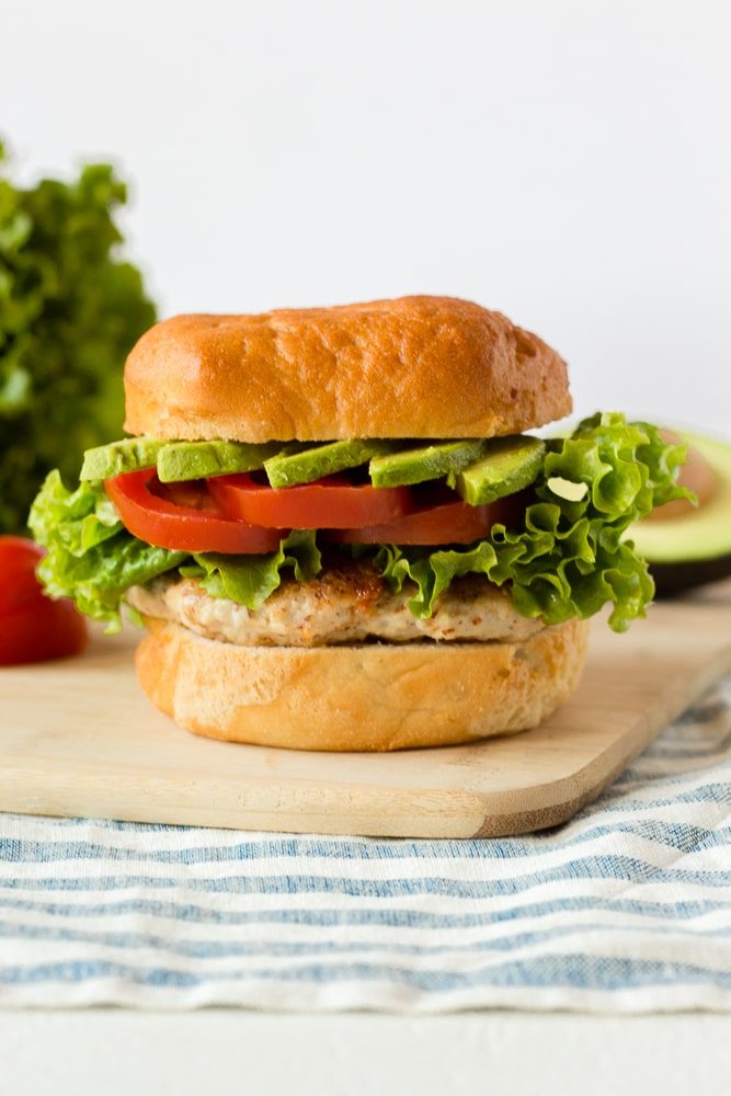 straight on shot of a healthy ground chicken burger with fixing in the background on top of a cutting board