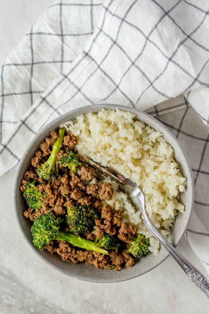 top down shot of paleo ground beef and broccoli stir fry in gray bowl with a fork in it