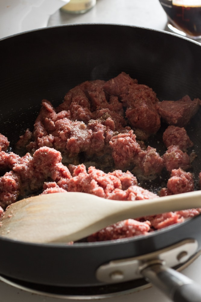 ground beef cooking in a black pan with a wooden spoon for paleo beef and broccoli stir fry