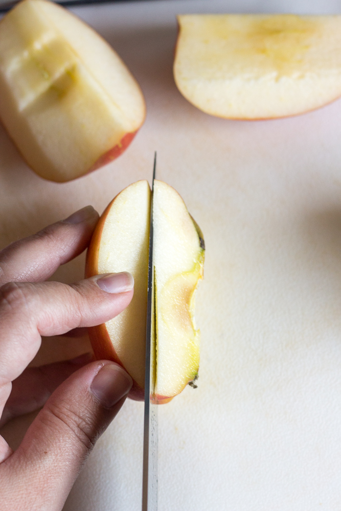 a knife cutting into a quartered apple