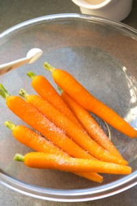 kosher salt poured onto carrots in plastic bowl