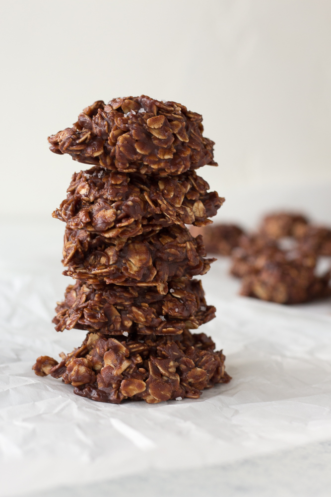 stack of no bake chocolate oatmeal peanut butter cookies on white parchment