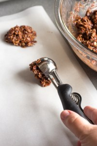placing a scoop of no bake chocolate oatmeal peanut butter cookies onto parchment paper