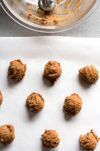 cookie dough balls on parchment paper with an empty bowl beside.