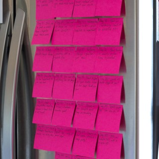 pink post it notes on a silver fridge
