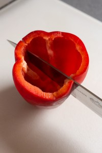 cutting a red bell pepper into two halves